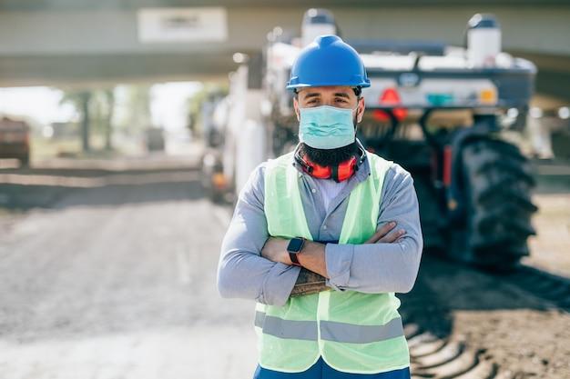 Junger männlicher straßenbauarbeiter mit gesichtsschutzmaske an seinem arbeitsplatz. heller sonniger tag. starkes licht.