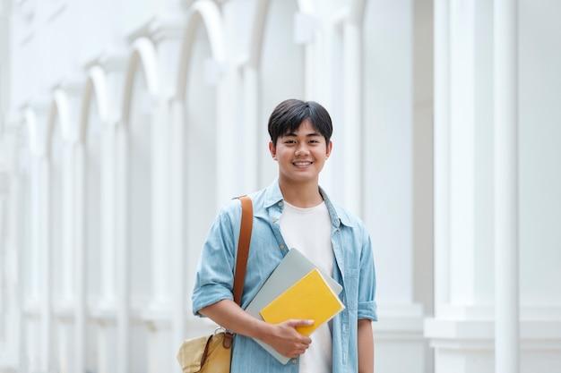Junger männlicher student am universitätscampus. zurück zum schulkonzept.