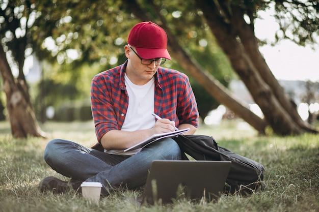 Junger männlicher student, der an einem computer im park arbeitet