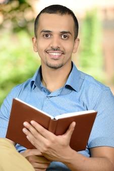 Junger männlicher student, der draußen ein buch im park liest.