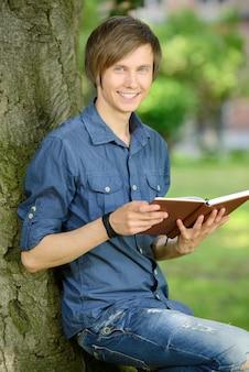 Junger männlicher student, der ein buch und ein lächeln liest.