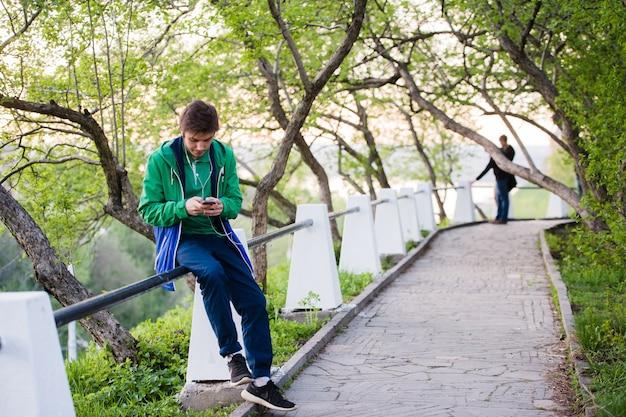 Junger männlicher student, der im park bei sonnenuntergang sitzt und handy hört, das musik hört. weiches licht und vintage-farbe