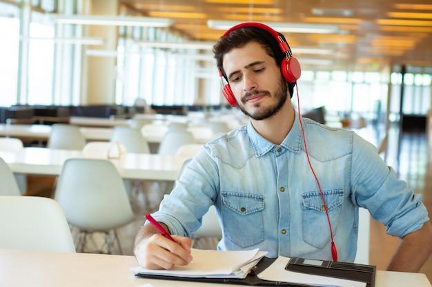 Junger männlicher student, der in der bibliothek studiert.