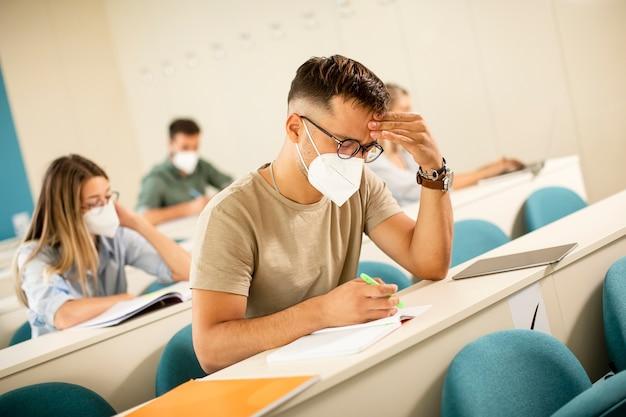 Junger männlicher student, der medizinische gesichtsschutzmaske für virenschutz am hörsaal trägt