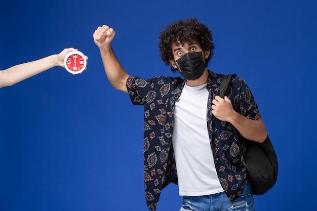 Junger männlicher student der vorderansicht, der schwarze maske mit rucksack auf hellblauem hintergrund trägt.