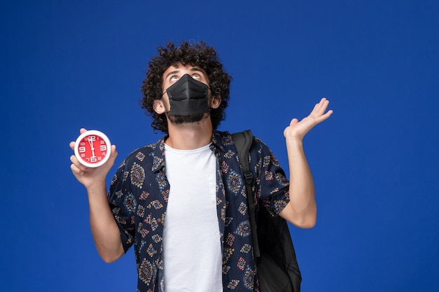Junger männlicher student der vorderansicht, der schwarze maske mit rucksack hält uhren auf blauem hintergrund trägt.