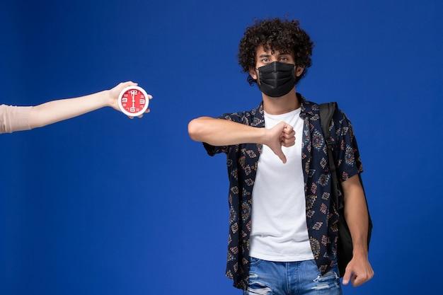 Junger männlicher student der vorderansicht, der schwarze maske mit rucksack trägt, der im gegensatz zum zeichen auf hellblauem hintergrund zeigt.