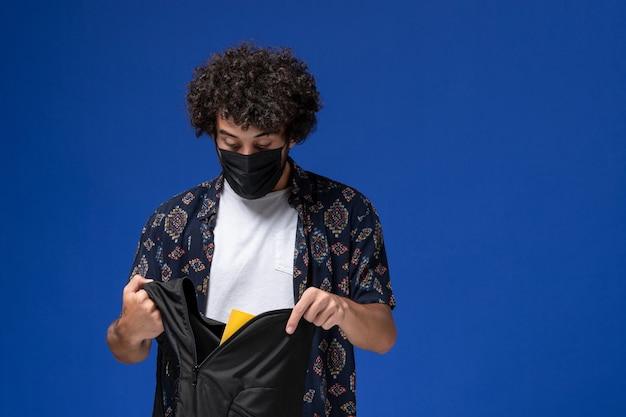 Junger männlicher student der vorderansicht, der schwarze maske trägt und rucksack auf hellblauem hintergrund hält.