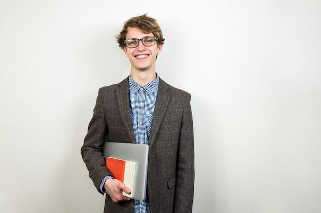 Junger männlicher student in tweedjacke und laptop mit buch