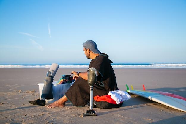 Junger männlicher surfer, der nahe brett am strand sitzt und künstliche gliedmaßen ändert