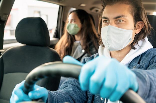 Junger männlicher taxifahrer in den schutzhandschuhen und in der maske, die durch lenken sitzen