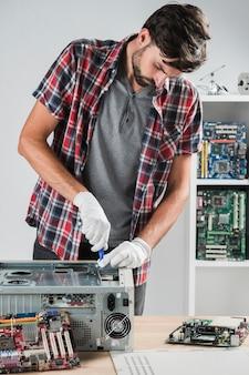 Junger männlicher techniker, der an computer-cpu in der werkstatt arbeitet