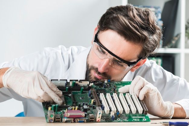 Junger männlicher techniker, der chip in computermotherboard auf hölzernem schreibtisch einfügt