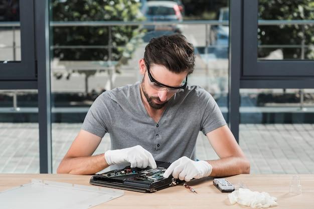 Junger männlicher techniker, der computer in der werkstatt repariert