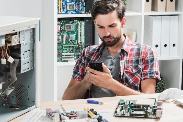 Junger männlicher techniker, der handy in der werkstatt verwendet