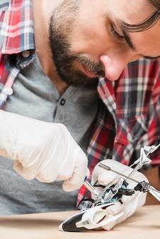 Junger männlicher techniker, der hubschrauberspielzeug repariert