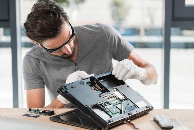 Junger männlicher techniker, der laptop auf hölzernem schreibtisch repariert