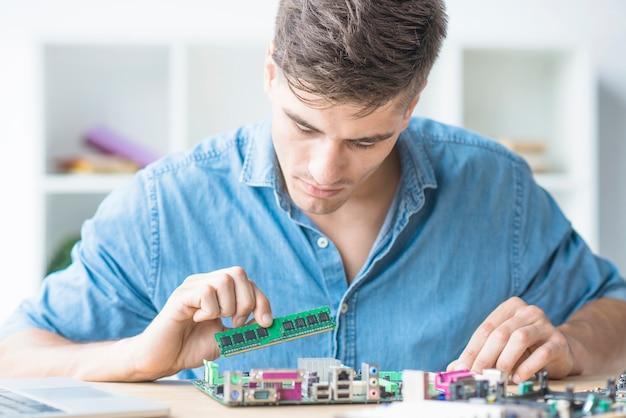 Junger männlicher techniker, der ram im motherboard repariert