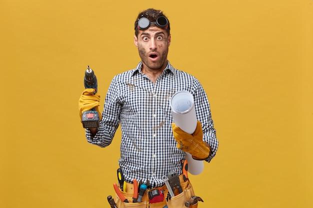Junger männlicher techniker mit schmutzigem gesicht, das schutzhandschuhe trägt, die bohrmaschine und blaupause in seinen händen halten, die schockierten ausdruck erkennen, wie viel er tun sollte