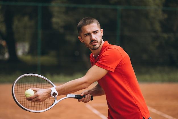Junger männlicher tennisspieler am gericht