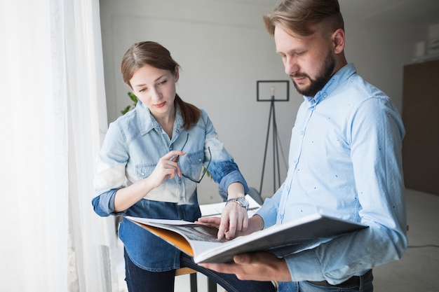 Junger männlicher und weiblicher architekt, der im büro arbeitet