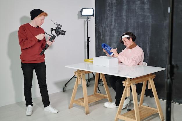 Junger männlicher vlogger, der neues schuhwerk vor seinem freund mit videokamera betrachtet, die ihn im studio schießt