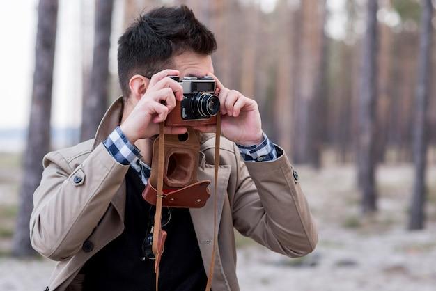 Junger männlicher wanderer, der fotos mit kamera macht