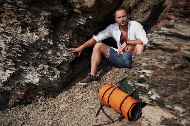 Junger männlicher wanderer mit rucksack, der auf einem felsigen massiv während des ruhigen sommersonnenuntergangs entspannt. travel lifestyle abenteuer urlaub konzept