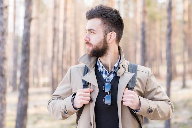 Junger männlicher wanderer mit seinem rucksack, der weg schaut