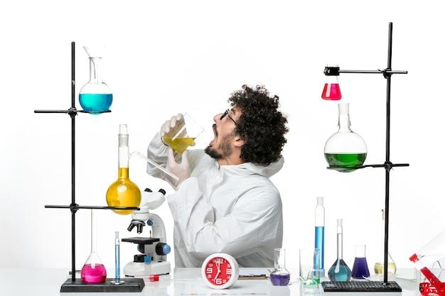 Junger männlicher wissenschaftler der vorderansicht im speziellen anzug sitzend mit lösungen, die auf weißer wand trinken