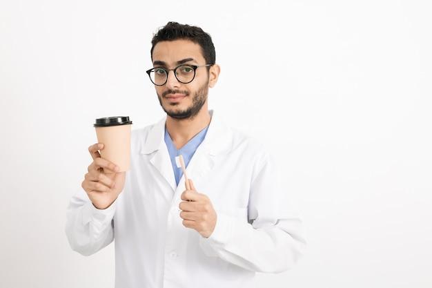 Junger männlicher zahnarzt im weißen kittel und in den brillen, die glas kaffee und zahnbürste halten, während sie isoliert betrachten