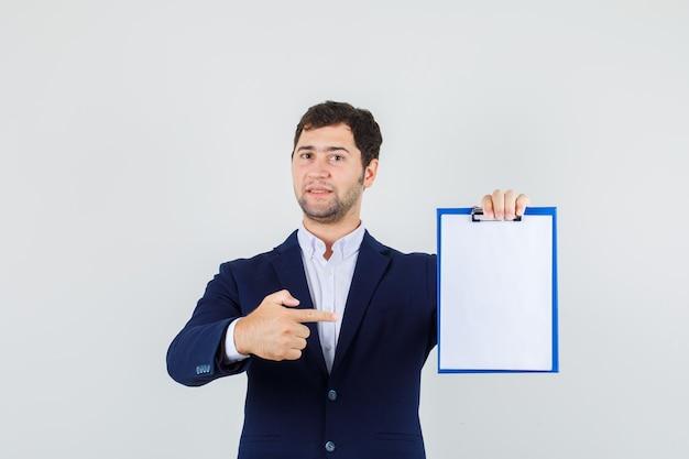 Junger männlicher zeigefinger auf zwischenablage im anzug und selbstbewusstsein, vorderansicht.