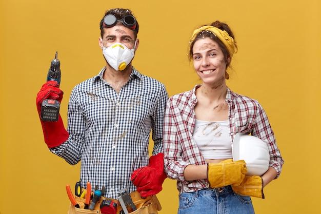 Junger männlicher zimmermann, der schutzbrille und maske hält bohrmaschine trägt, die mit verschiedenen werkzeugen für das bauen in der nähe seiner frau ausgestattet ist, die erfreuten ausdruck während der arbeit hat