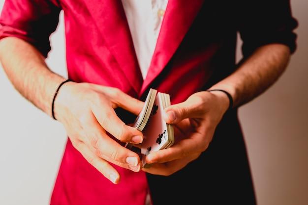 Junger magier, der ein kartenspiel jongliert.