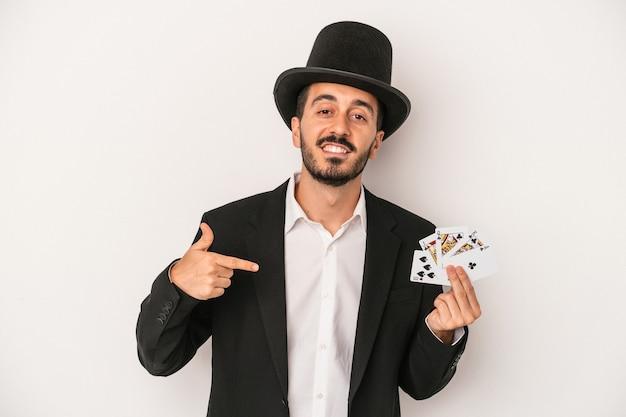 Junger magiermann, der eine magische karte einzeln auf weißem hintergrund hält, die mit der hand auf einen hemdkopierraum zeigt, stolz und selbstbewusst