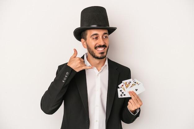 Junger magiermann, der eine magische karte lokalisiert auf weißem hintergrund hält, der eine handyanrufgeste mit den fingern zeigt.