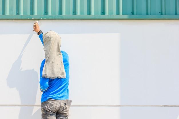 Junger maler, der eine wand mit pinseln malt