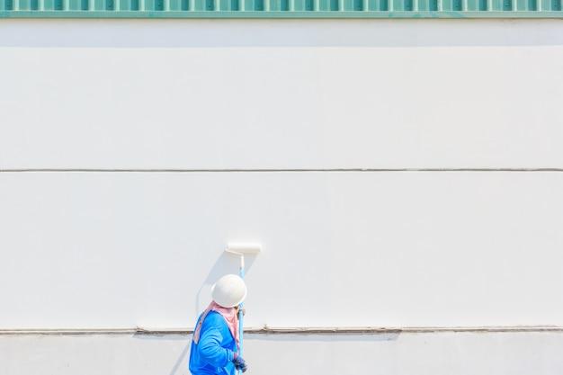 Junger maler mit blauer kappe und handschuhe, die eine wand mit farbenrolle malen