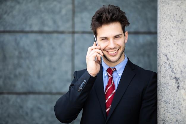 Junger manager am telefon im freien in einer städtischen umgebung