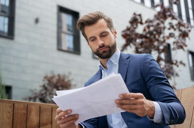 Junger manager, der ein projekt plant, das einen finanzbericht hält, der erfolgreich arbeitet