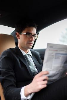 Junger manager, der eine zeitung auf dem rücksitz eines autos liest