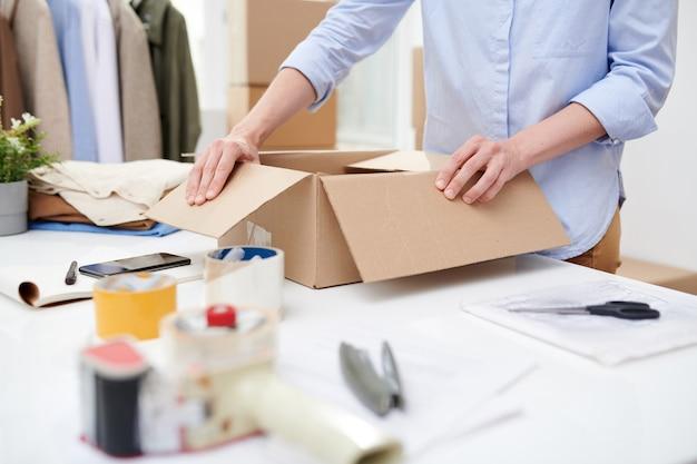 Junger manager des online-shop-büros, der karton nach arbeitsplatz öffnet, bevor bestellung des kunden verpackt wird