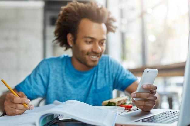 Junger manager männlich, der drinnen sitzt, der notizen unter verwendung des modernen telefons und des laptops für das lösen von arbeitsproblemen schreibt.