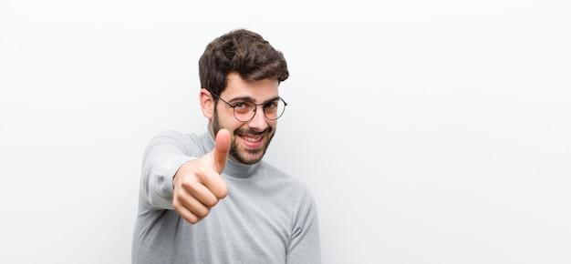 Junger manager mann, der stolz, sorglos, selbstbewusst und glücklich fühlt und positiv mit daumen gegen weiße wand lächelt