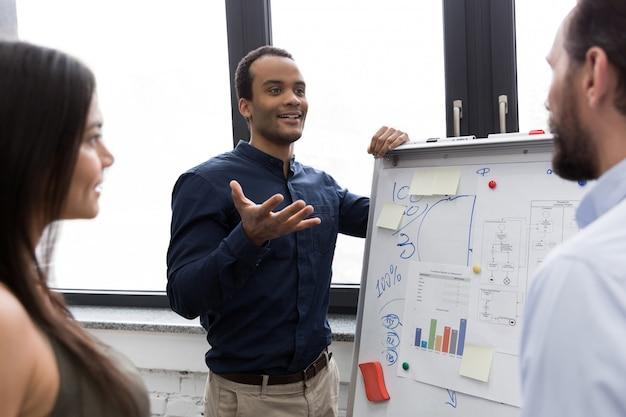 Junger manager präsentiert seinen kollegen whiteboard