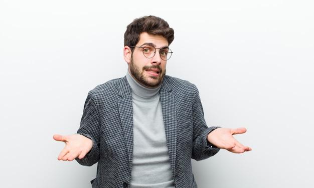 Junger managermann, der ahnungslos und verwirrt sich fühlt, nicht sicher, welche wahl oder wahl man auswählt und gegen weiße wand sich wundert
