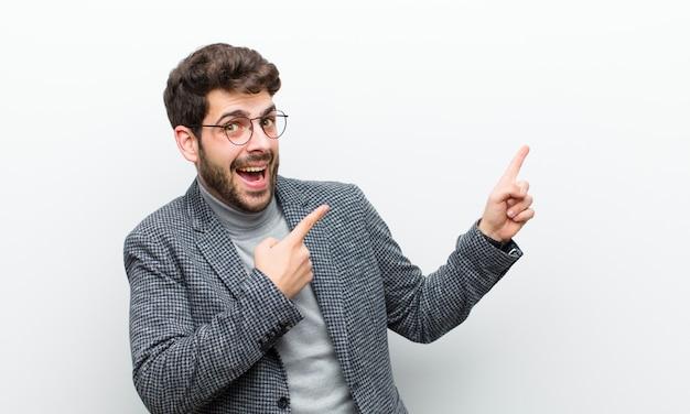 Junger managermann, der froh und überrascht sich fühlt, mit einem entsetzten ausdruck lächelt und auf die seite gegen weiße wand zeigt