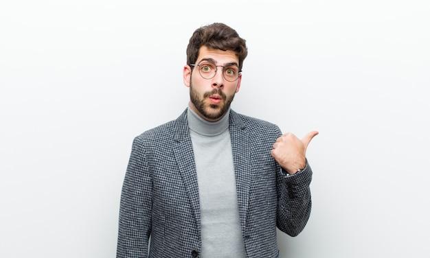 Junger managermann, der im unglauben erstaunt schaut, auf gegenstand auf der seite zeigt und wow, unglaublich gegen weiße wand sagt