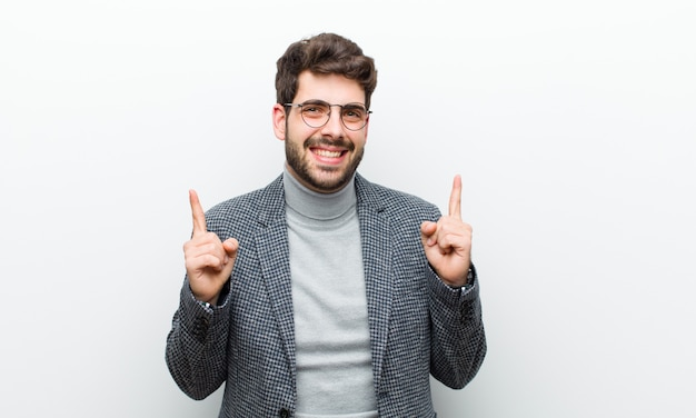 Junger managermann, der mit ehrfurcht und offenem mund zeigt aufwärts mit einem entsetzten und überraschten blick gegen weiß sich fühlt