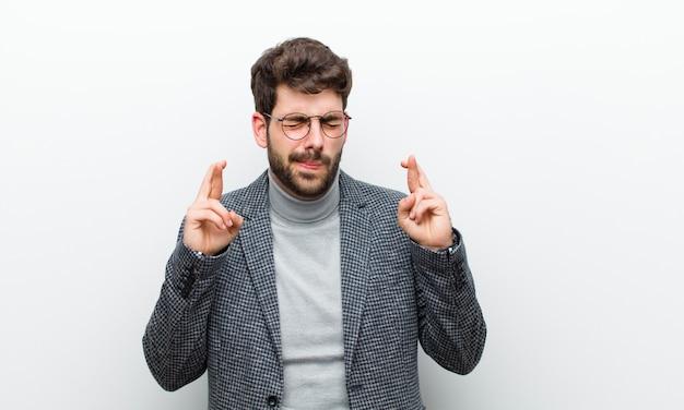 Junger managermann, der nervös und hoffnungsvoll sich fühlt, finger kreuzt, für gutes glück betet und hofft